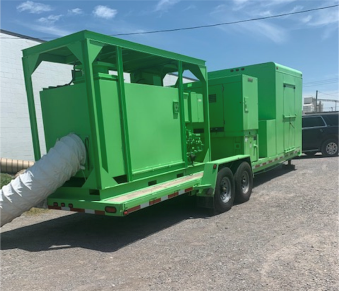 Large green drying equipment in parking lot outside warehouse