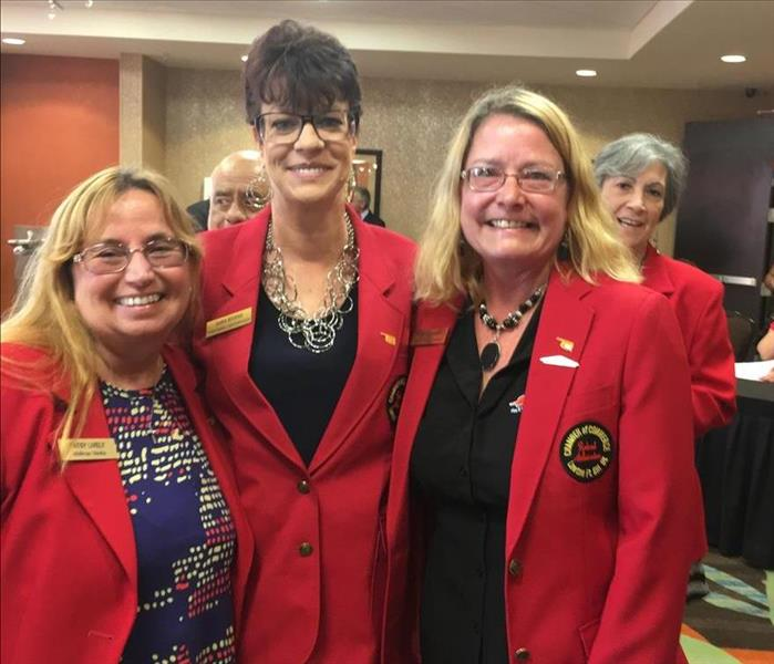 Three ladies in red coats welcome meeting attendees