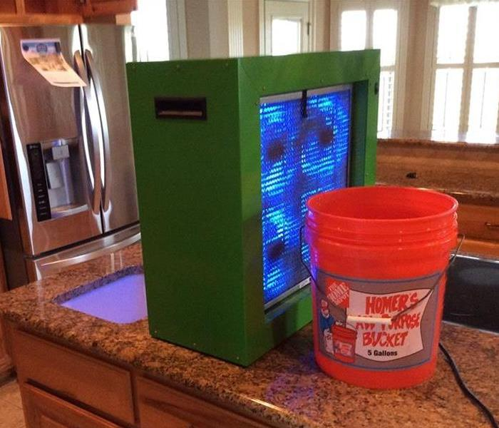 green box and orange 5 gallon bucket on kitchen counter